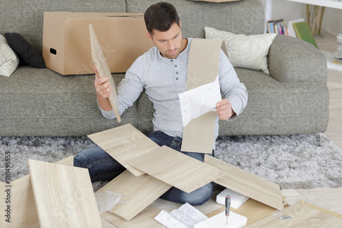 Man surrounded by pieces of flat pack furniture