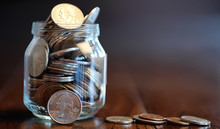 Coins In A Glass Jar On A Wood...