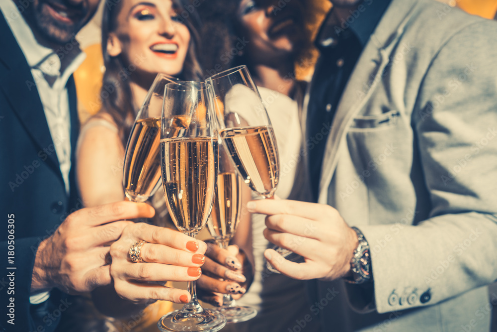 Fototapeta Men and women celebrating birthday or new years party while clinking glasses with sparkling wine