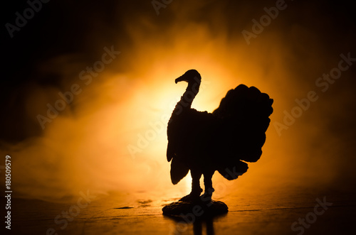 Statue of Turkey Tom strutting his stuff with red wattles and blue/white head on a smoke toned dark background Wallpaper Mural