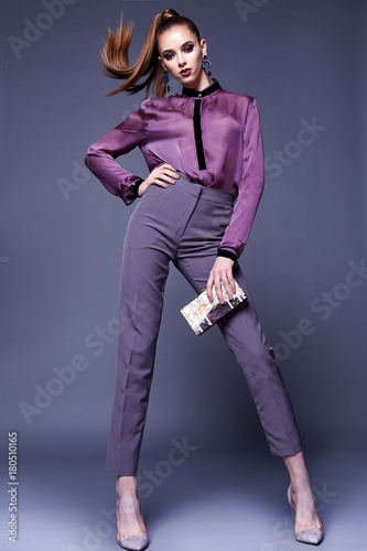 Beautiful business woman lady style perfect body shape brunette jewelry earrings wear fashion clothes lilac silk blouse pants portrait cosmetic make up accessory bag glamour model pose party office.