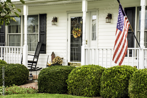 Fotografía  white colonial home decorated for fall with American flag flying from the front