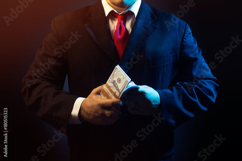 Valokuva Mafia man in suit counting money on black background.