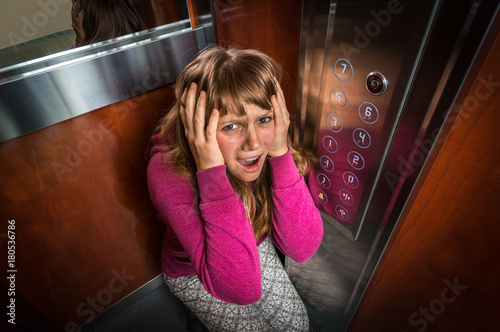 Shocked woman with claustrophobia in the moving elevator Wallpaper Mural