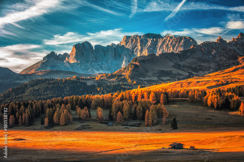 Aerial autumn sunrise scenery with yellow larches and small alpine building and Odle - Geisler mountain group on background. Alpe di Siusi (Seiser Alm), Dolomite Alps, Italy