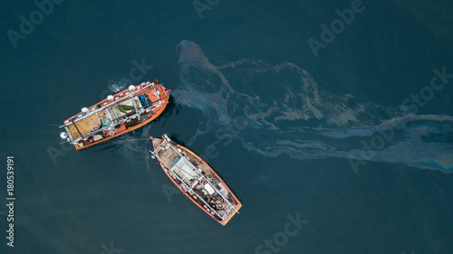 Stampa su Tela  Fishing boats and oil spill