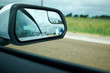 Blue truck in the side mirror on highway