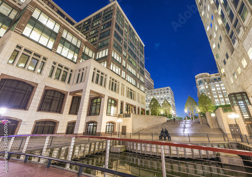 Buildings of Canary Wharf at night in London. View from the street