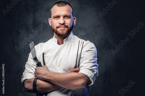Chef cook holds a knife over dark grey background.