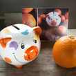 Postcard with a piggy bank and tangerines.