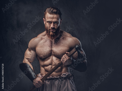 Photo  A man holds axe over dark grey background.