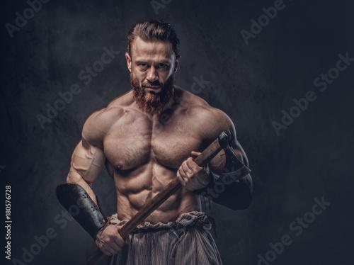 Fotografie, Obraz  A man holds axe over dark grey background.