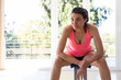 Attractive young woman in pink tank top sitting on bench in gym.
