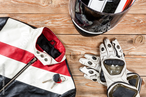 View of motorcycle rider accessories placed on rustic wooden table.