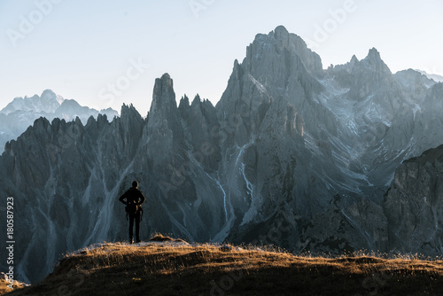 Young adult male standing and taking in the view in front of the dolomites mountains in italy - 180587923