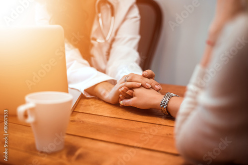 Fotografia  Doctor's hands holding female patient's hand for encouragement and empathy