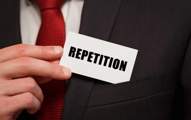 Businessman putting a card with text REPETITION in the pocket
