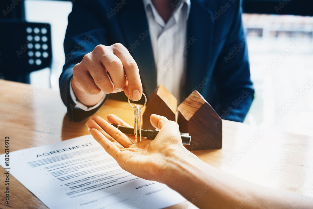 Fototapeta Real estate agents agree to buy a home and give keys to clients at their agency's offices. Concept agreement