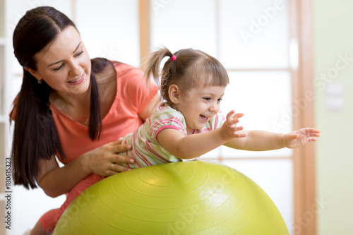 Fotografia Mother and baby playing with fitness ball