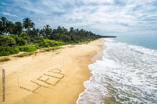 Carta da parati Uninhabited tropical island with word help in deserted beach, sos and shipwreck