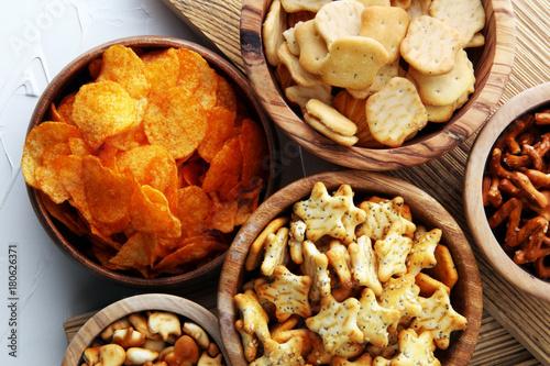 Leinwand Poster Salzige Snacks. Brezeln, Chips, Cracker in Holzschalen.