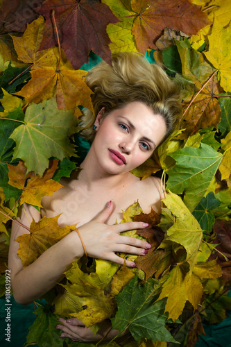 Fototapety, obrazy: The girl lays on autumn leaves
