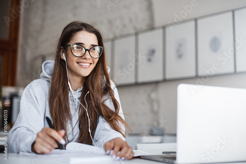 Young female teacher wearing glasses preparing for her class