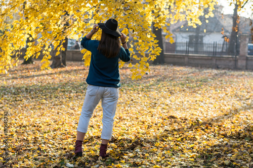 Fotografia  Woman with a hat leaning back under a tree with a yellow leaves