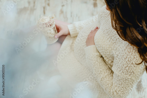 Foto op Canvas Bar Pregnant girl in a knitted sweater beige color sitting on floor and holding a small cell