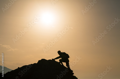 Fototapeta Climbing hiking silhouette in mountains over summer sunrise obraz na płótnie