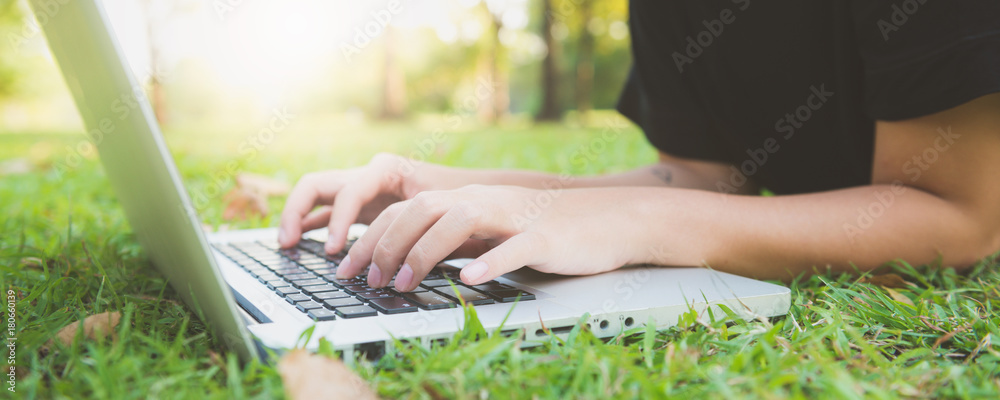 Fototapety, obrazy: Young asian woman's legs on the green grass with open laptop. Girl's hands on keyboard. Distance learning concept. Happy hipster young asian woman working on laptop in park. Panoramic banner.