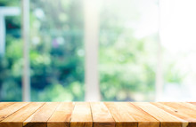 Wood Table Top On Blur Of Window With Garden Flower Background In Morning.For Montage Product Display Or Key Visual Layout