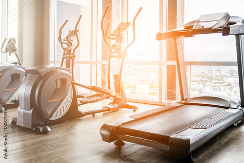 Fitness hall with elliptical and treadmill next to window with daylight morning Fototapeta