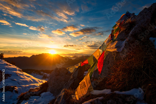 Photographie Flags of Tibetan prayers in the mountains with the colors of a warm sunset