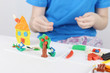 Child hands molding bright house, tree, flowers from plasticine on table in room