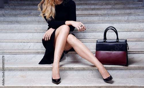 Cuadros en Lienzo Fashion model sitting in black dress with big bag high heel shoes