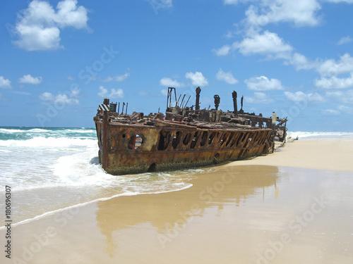 Obraz na płótnie rusty shipwreck on the beach with blue sky