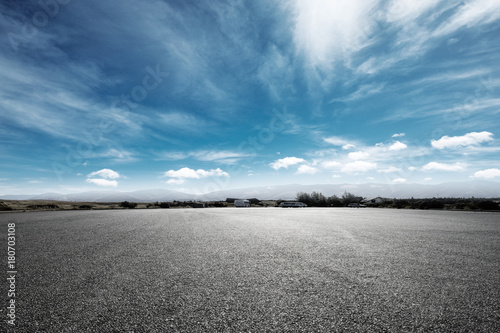 Poster Gris empty asphalt road with snow mountains in blue cloud sky