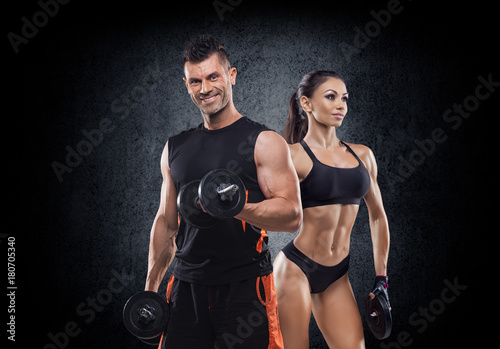 Fototapeta beautiful young sporty sexy couple showing muscle and workout in gym during phot