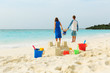 family beach vacation- sand castle and family at sea