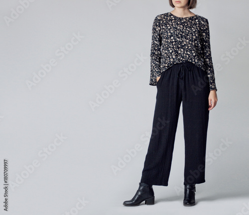 Obraz na plátně  Woman wearing stylish outfit with black patterned blouse, black high-waisted wide leg trousers and black ankle boots isolated on grey background