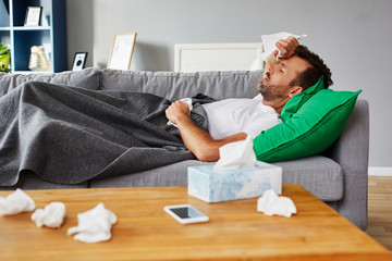 Sick man with fever lying on couch at home