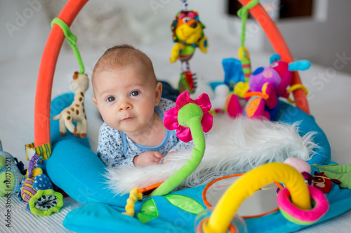 Cute baby boy on colorful gym, playing with hanging toys at home Fototapete