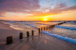 sunset over the sea beach, waves crashing on the stakes