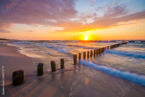 Spoed Foto op Canvas Zee zonsondergang sunset over the sea beach, waves crashing on the stakes