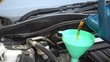Pouring fresh new synthetic oil into car engine.