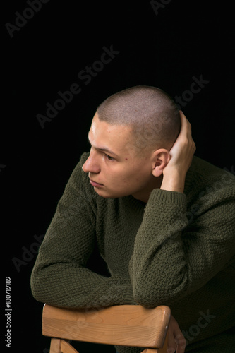 Fotografie, Tablou A young man is skinhead in a green military style sweater