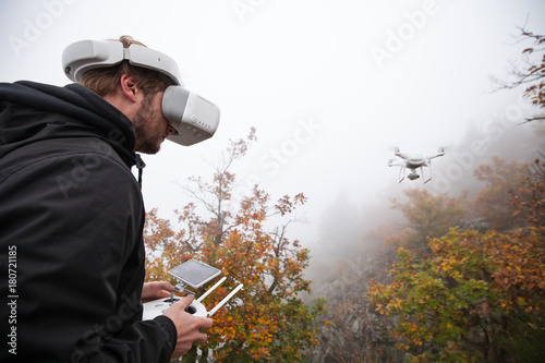 Young man handling drone, using virtual reality glasses.