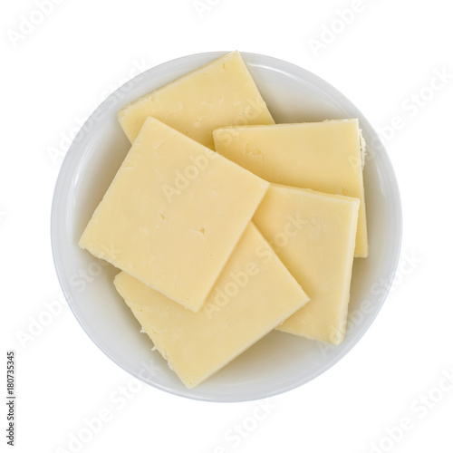 Top view of a small bowl filled with sharp cheddar cheese square slices isolated on a white background.