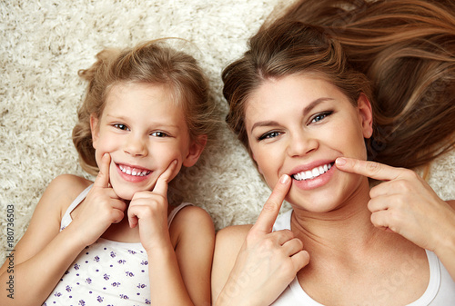 Fotografie, Obraz  Portrait of beautiful daughter with mom showing their healthy white smile lying on carpet at home
